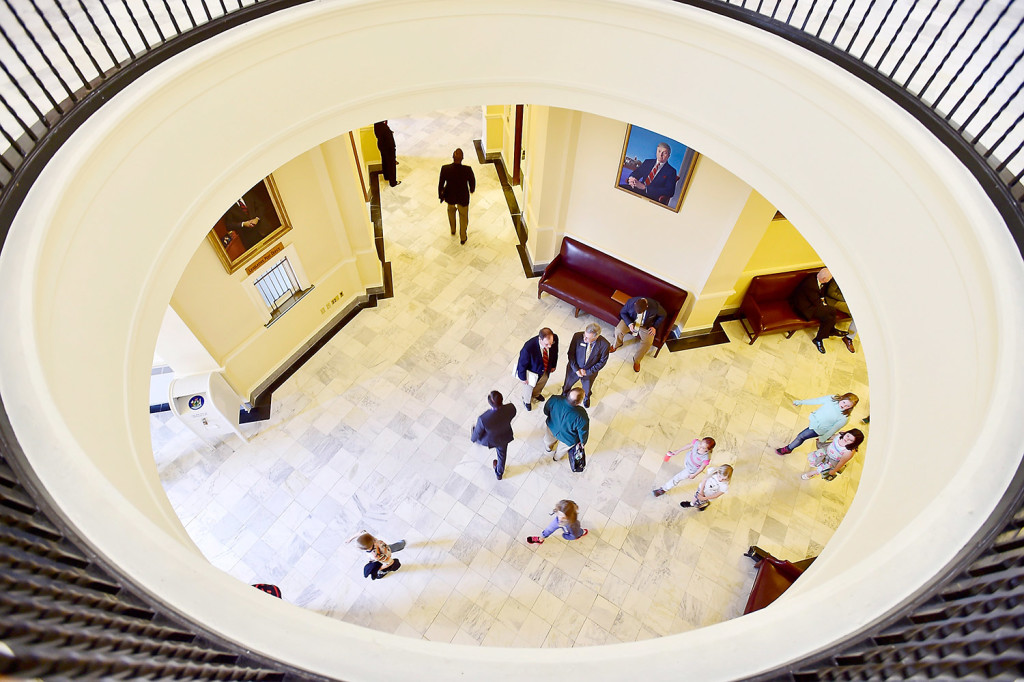 State legislators confer after the daily session as schoolchildren walk by in a tour of the State House on Friday. Republican legislators have submitted their own tax reform plan.