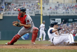 Minnesota's' Brian Dozier slide past Red Sox catcher Blake Swihart during the Twins' 7-2 win Monday. The Associated Press