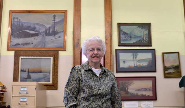 Lena Arno, with the Madison Historical and Genealogical Society, stands with art works created by local artist Willis Pelton on Friday,  May 8, 2015. The exhibit runs from 1pm to 4pm on Saturday and is free to the public.