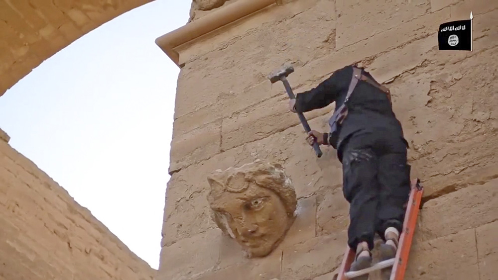 In this image from a militant video posted on YouTube on April 3, 2015, a militant hammers away at a face on a wall in Hatra, a large fortified city recognized as a UNESCO World Heritage site, 68 miles southwest of Mosul, Iraq. The Islamic State group's attacks on these famed archaeological treasures are partially motivated by the group's hostility to non-Islamic and pre-Islamic cultures. But some antiquities authorities have charged that the destruction is a partial cover for the militants' lucrative business in selling looted artifacts on the black market.