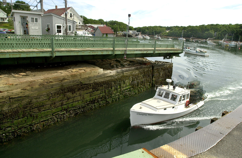 A lobster boat passes through the Gut Passage in South Bristol, one of Maine's last remaining swing bridges. Cianbro has a contract to replace the bridge and needs skilled workers for that job and many other projects in Maine and along the Eastern Seaboard. Press Herald file photo