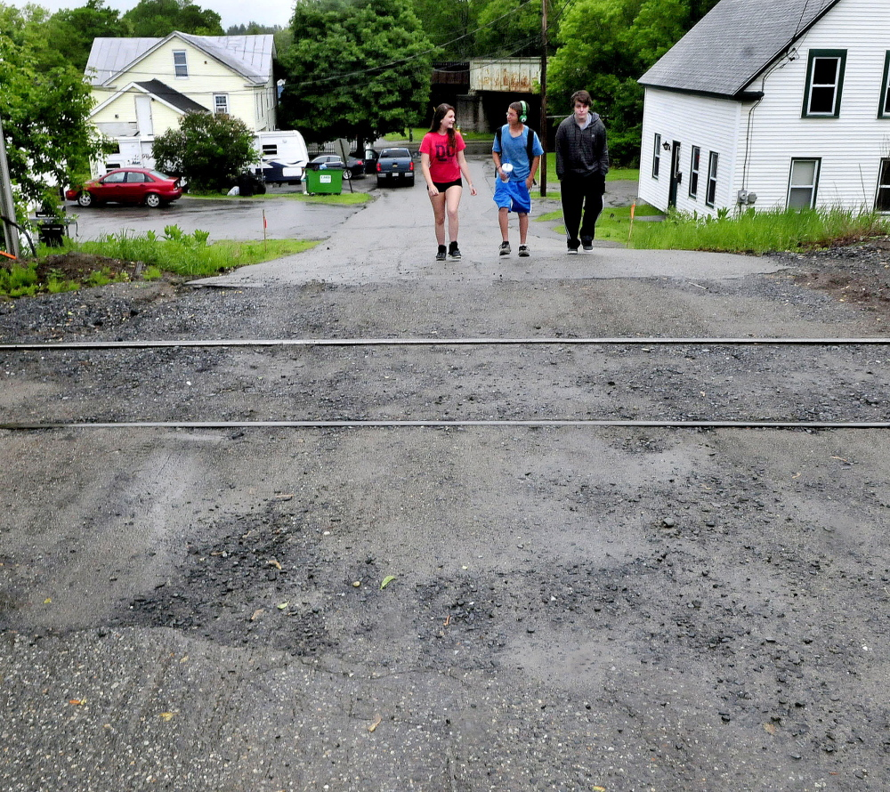 By this summer only foot traffic will be allowed near the railroad tracks on Elm Street in Fairfield after the rail crossing is closed off to vehicle traffic. Vehicles will still have access to homes on either side of the tracks, but won't be able to cross the tracks. Walking on Monday are, from left, Ashley Leighton, Devyn Fecteau and Mason Worden.
