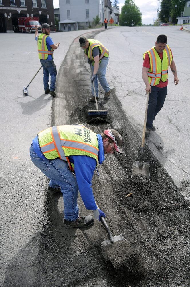 Augusta Public Works employees collect pavement chipped from the shoulder of Water Street in front of Hartford Fire Station in Augusta in this May 20 file photo. Paving in that area is scheduled for Wednesday and Thursday.