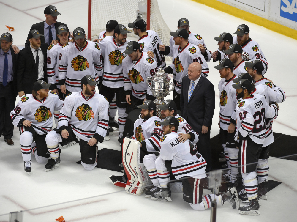 Members of the Chicago Blackhawks pose around the trophy after their win against the Anaheim Ducks in Game 7 of the Western Conference final of the NHL hockey Stanley Cup playoffs in Anaheim, Calif., on Saturday. The Blackhawks won 5-3 to advance to Stanley Cup Finals.