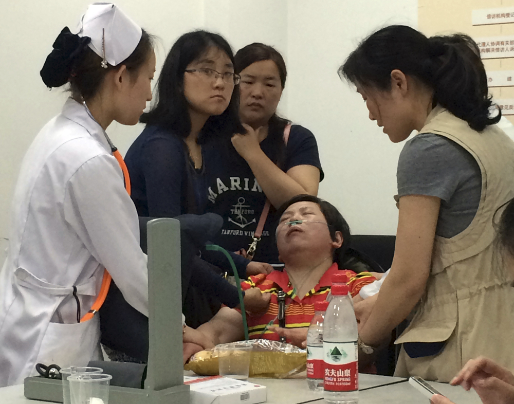 A relative of Shanghai passengers on board a cruise ship that capsized in central China, is attended to by a medical worker as she waits for answers at a government office in Shanghai, China, Tuesday.