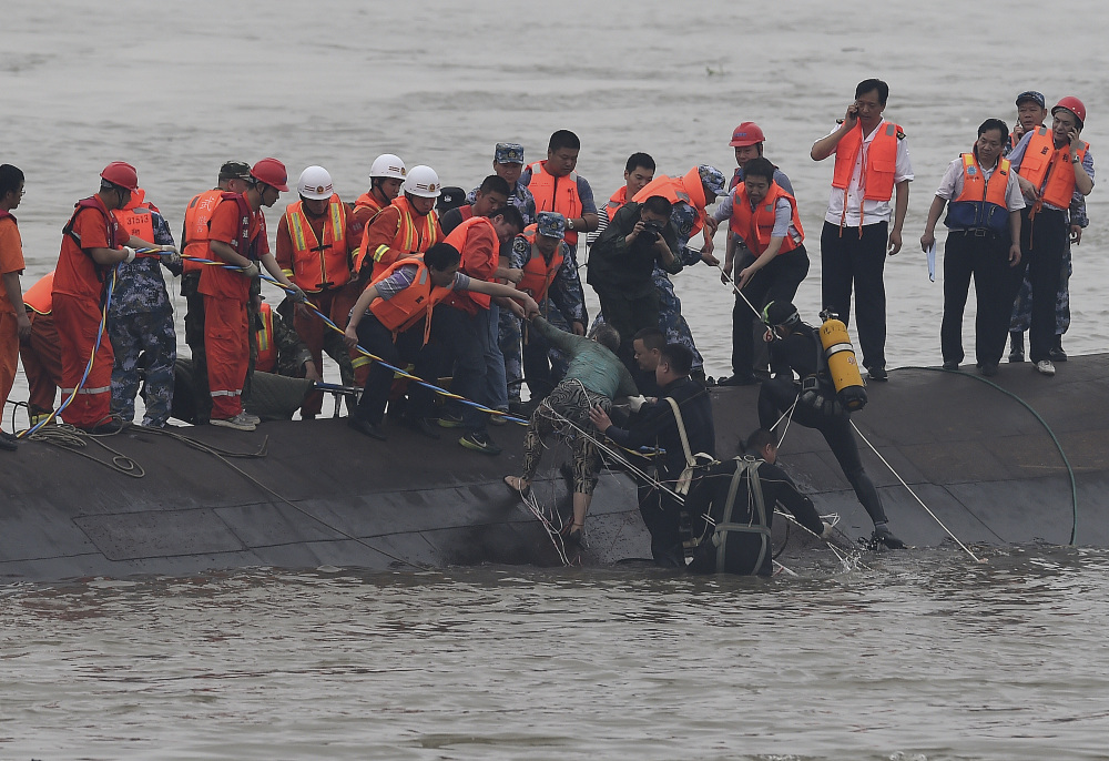 In this photo released by China's Xinhua News Agency, rescuers save a survivor, center, from the overturned passenger ship in the Jianli section of the Yangtze River in central China's Hubei Province Tuesday.