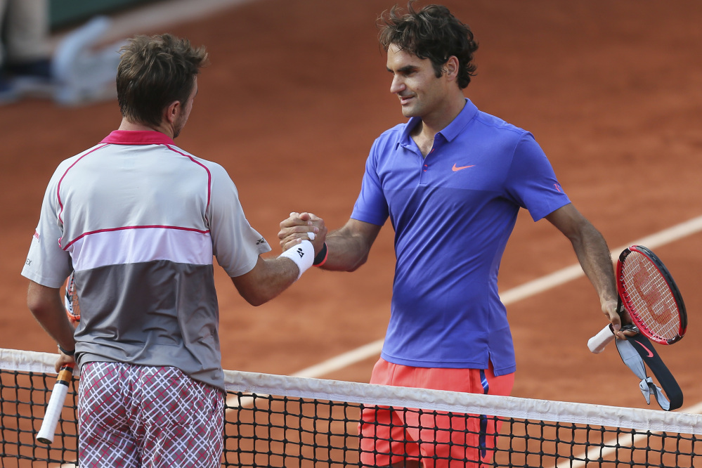 Stan Wawrinka shakes hands with compatriot Roger Federer, right, after winning the quarterfinal match Tuesday of the French Open in three sets 6-4, 6-3, 7-6 (7-4), at the Roland Garros stadium, in Paris, France.