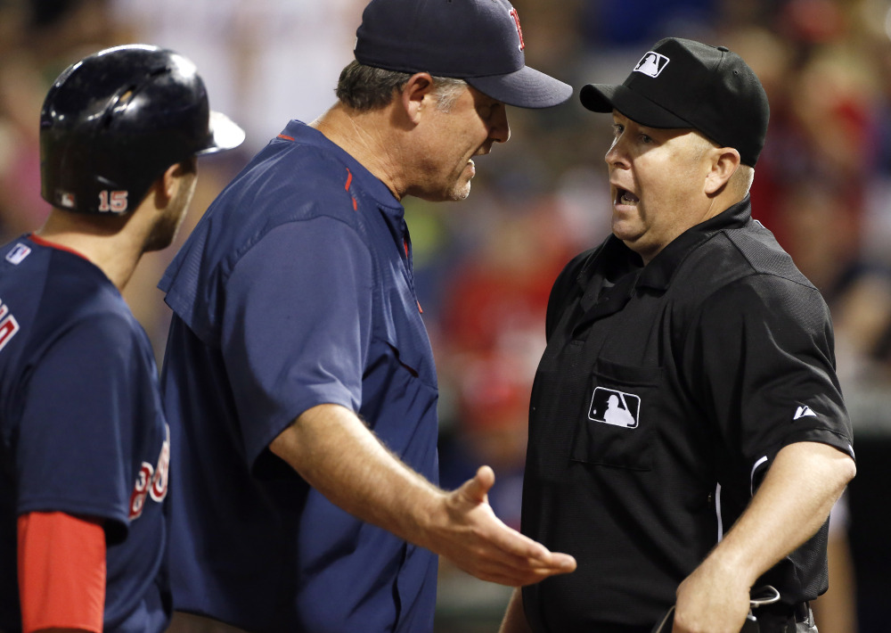 Boston Red Sox manager John Farrell, center, argues a strike three call against Dustin Pedroia, left, to home plate umpire Todd Tichenor last week in Arlington, Texas. Texas won 7-4. Red Sox owner John Henry said the his is disappointed in the team's play, but added that the jobs of Farrell and GM Ben Cherington are safe.