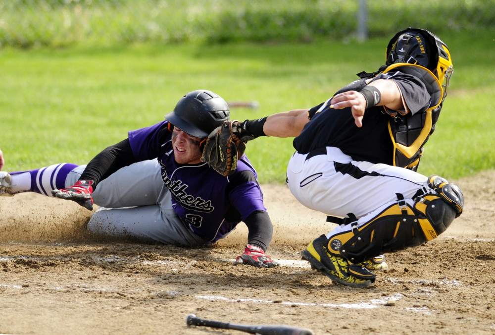 Waterville's Dan Pooler slides safely into home avoiding te tag by Maranacook catcher Mark Buzzell during a game Wednesday in Readfield.