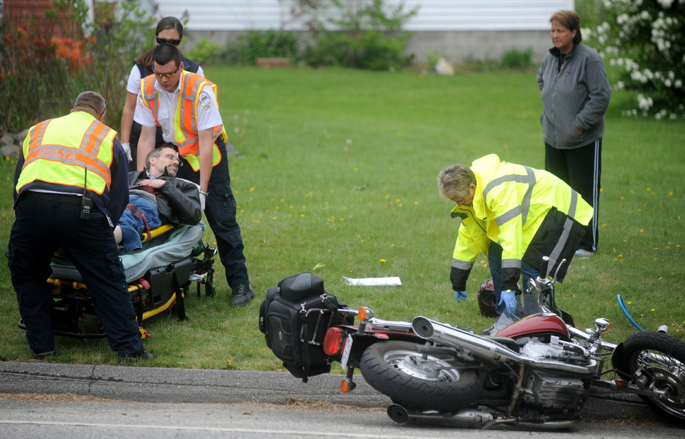 Emergency responders from the Sidney Fire Department and Delta Ambulance treat a motorcyclist whose motorcycle was hit Thursday by a car on West River Road in Sidney.