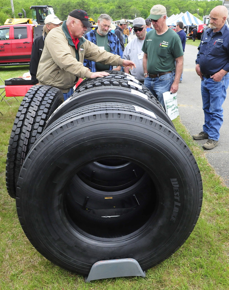 Participants in the American Public Works Highway Congress check out tires for sale Thursday at the Skowhegan Fairgrounds.