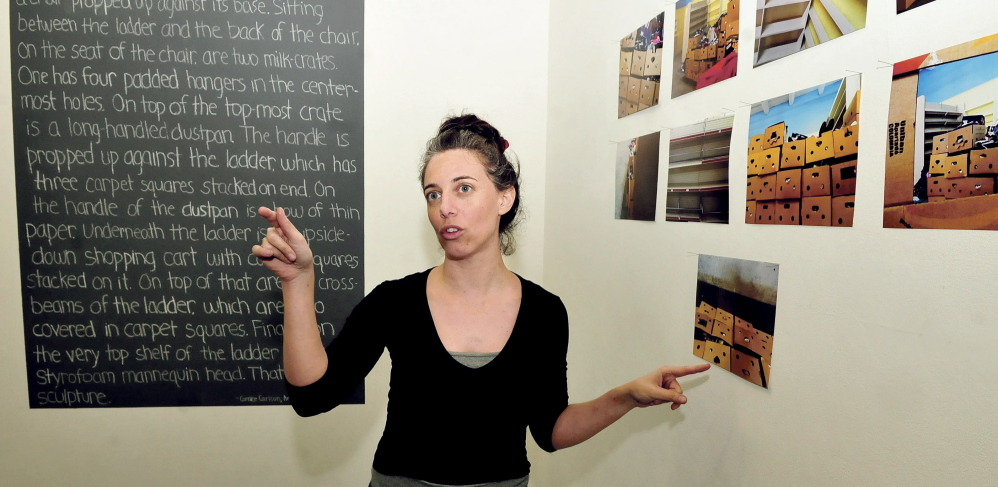 Colby College artist in residence Shirel Horovitz hangs an art exhibit Wednesday by area students she worked with at Common Street Arts in Waterville. The exhibit opened Thursday and runs through Sunday.