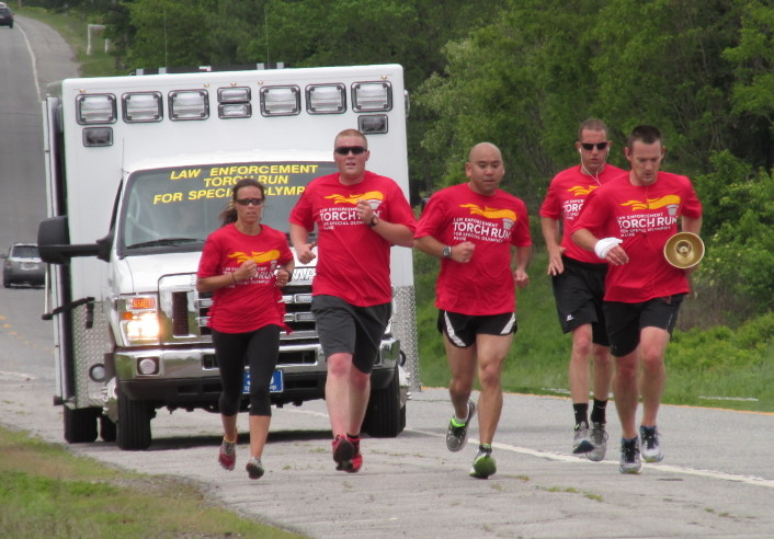 Law enforcement officers carry the Special Olympics torch Thursday down U.S. Route 2. The run began May 26 in Augusta and culminates Friday at the Special Olympics Maine Summer Games in Orono.