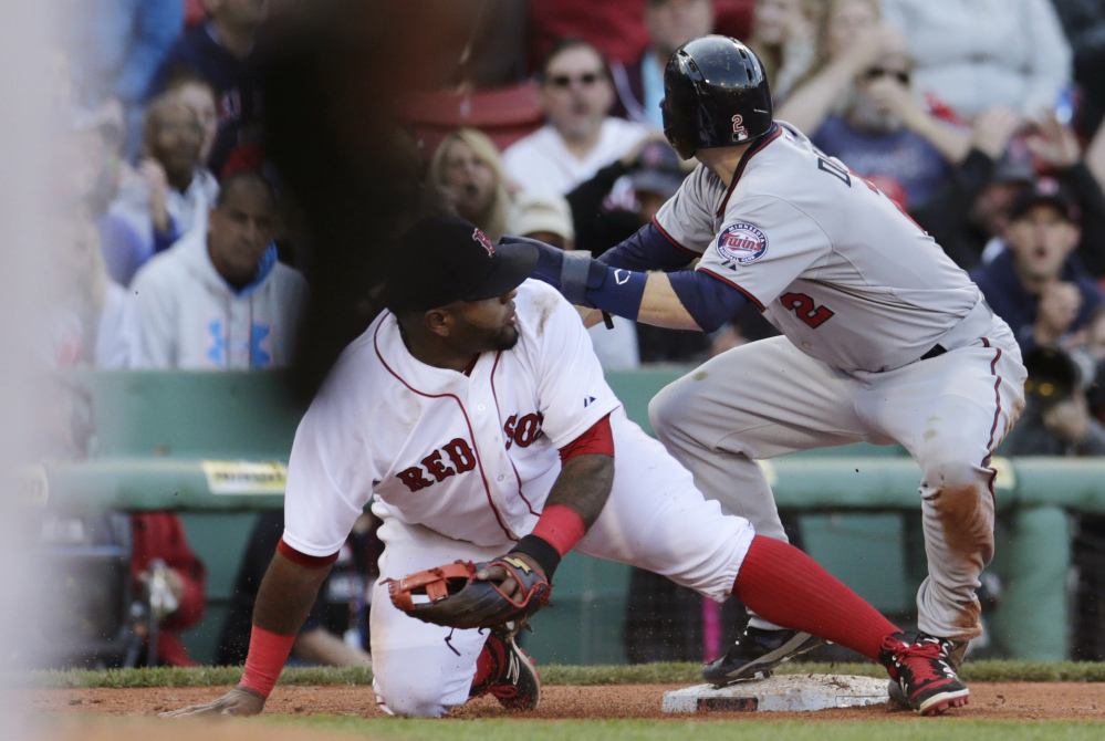 Boston Red Sox third baseman Pablo Sandoval drops to a knee after mishandling a throw from catcher Blake Swihart, which allowed Minnesota Twins' Brian Dozier, right, to score, breaking a 4-4 tie during the ninth inning Thursday in Boston. The Twins defeated the Red Sox 8-4.