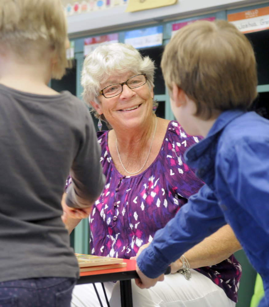 Hall-Dale Elementary School pre-kindergarten teacher Sue Dodge speaks with a pair of students earlier this week after helping them lace their sneakers in her class at the Hallowell school. Dodge is retiring after teaching for more than 40 years at the elementary level at Hall-Dale.