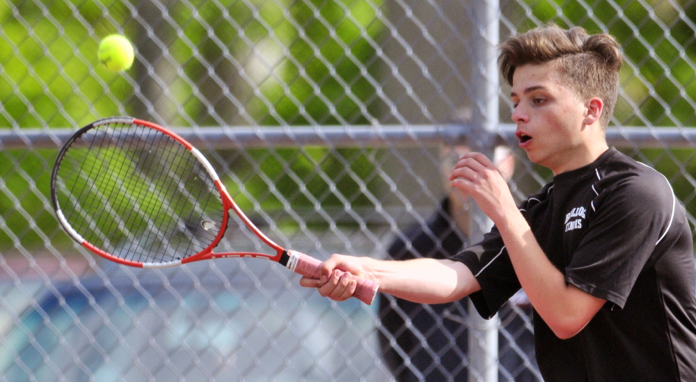 Staff photo by Joe Phelan Hall-Dale's Thomas Plourde returns a shot during a doubles match against St. Dominic's Matt Boulet and Cam Jalbert in a Western C semifinal Friday at Hall-Dale. The Saints won the match 1-6, 7-5, 6-2.