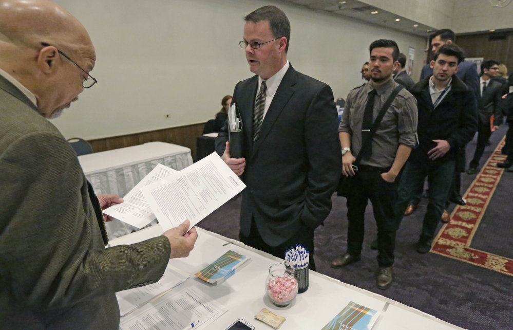 Ralph Logan, general manager of Microtrain, left, speaks with James Smith who is seeking employment during a National Career Fairs job fair in Chicago. The U.S. economy is churning out a lot of jobs but not a lot of financial security for many of the people who hold them.