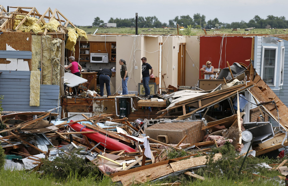 Members of the Eyl family salvage items from their home, which was destroyed in the previous night's tornado, southwest of the town of Berthoud, Colo., on Friday.