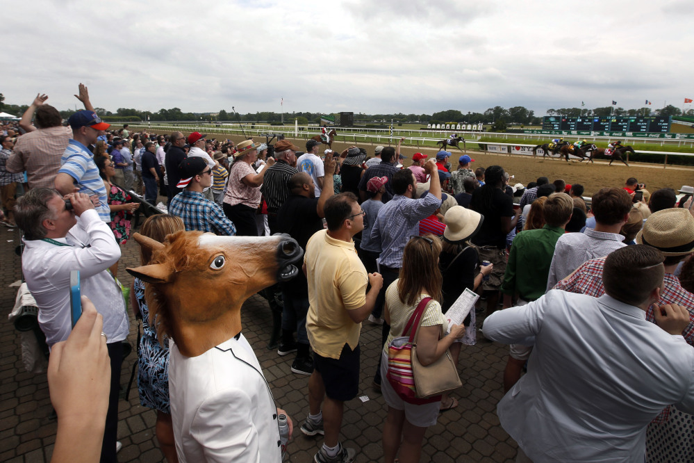 AP photo   A spectator wearing a horse mask watches the third race of the day on Saturday prior to the 147th running of the Belmont Stakes in Elmont, N.Y.