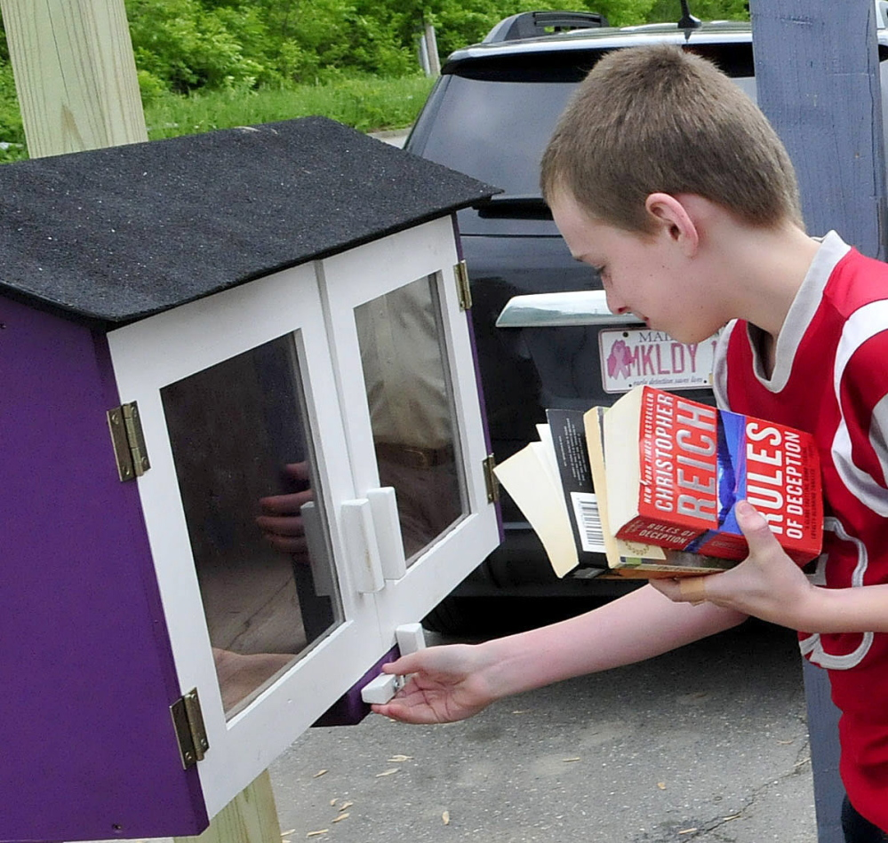 Holding an armload of books Wednesday, Logan O'Neal opens the doors of the Little Free Library near the South End Teen Center in Waterville.