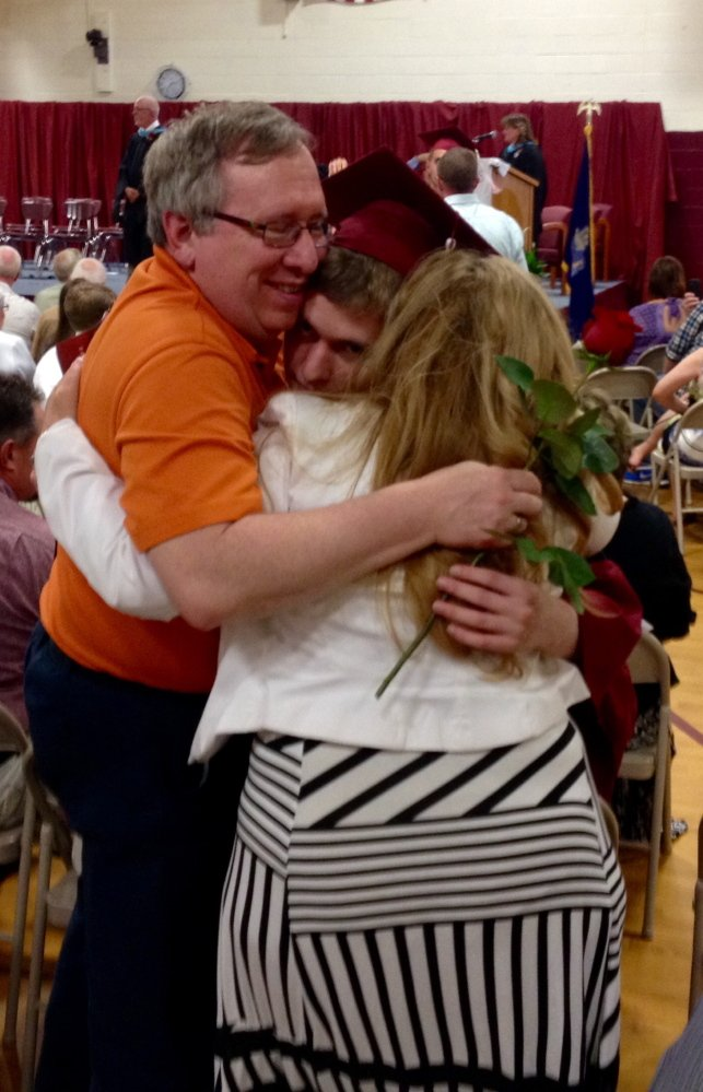 Richmond High School senior Erik Sanford hugs his parents, Alan and Deborah Sanford, during the graduation ceremony Saturday in the school gymnasium in Richmond.