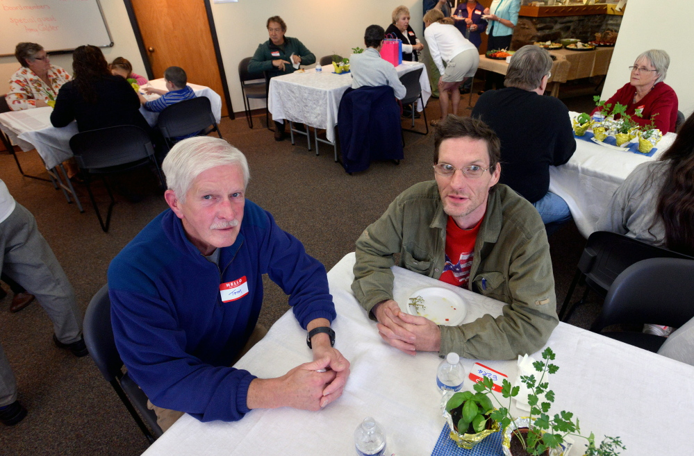 Tom McGuire, left, sits with his student, Ezra Randall Jr., during the annual meeting of Literacy Volunteers Waterville in the Colby Room at Waterville Public Library on Tuesday.