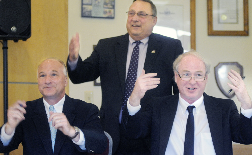 University of Maine Chancellor James Page, right, and Maine Community College System interim President Derek Langhauser and Gov. Paul LePage ask students to join them Monday in applauding the signing of an agreement to expedite the transfer of academic credits between the higher education systems.