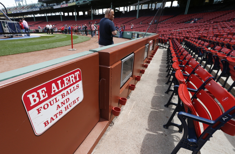 A warning sign is displayed in the stands at Fenway Park before a baseball game between the Boston Red Sox and the Oakland Athletics on Saturday in Boston. Tonya Carpenter of Paxton, Mass., was hit and seriously injured by a broken bat during the game Friday.