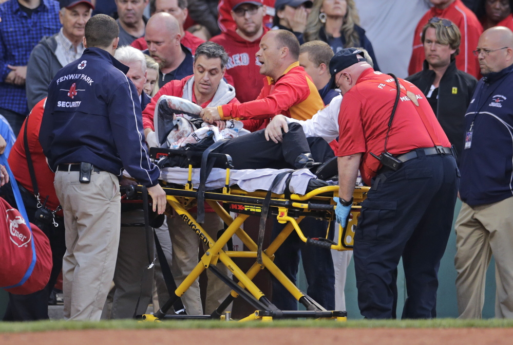 Tonya Carpenter, who was accidentally hit in the head with a broken bat by Oakland's Brett Lawrie, is helped from the stands during a game against the Boston Red Sox on Friday at Fenway Park in Boston. The game was stopped while they wheeled her down the first base line.