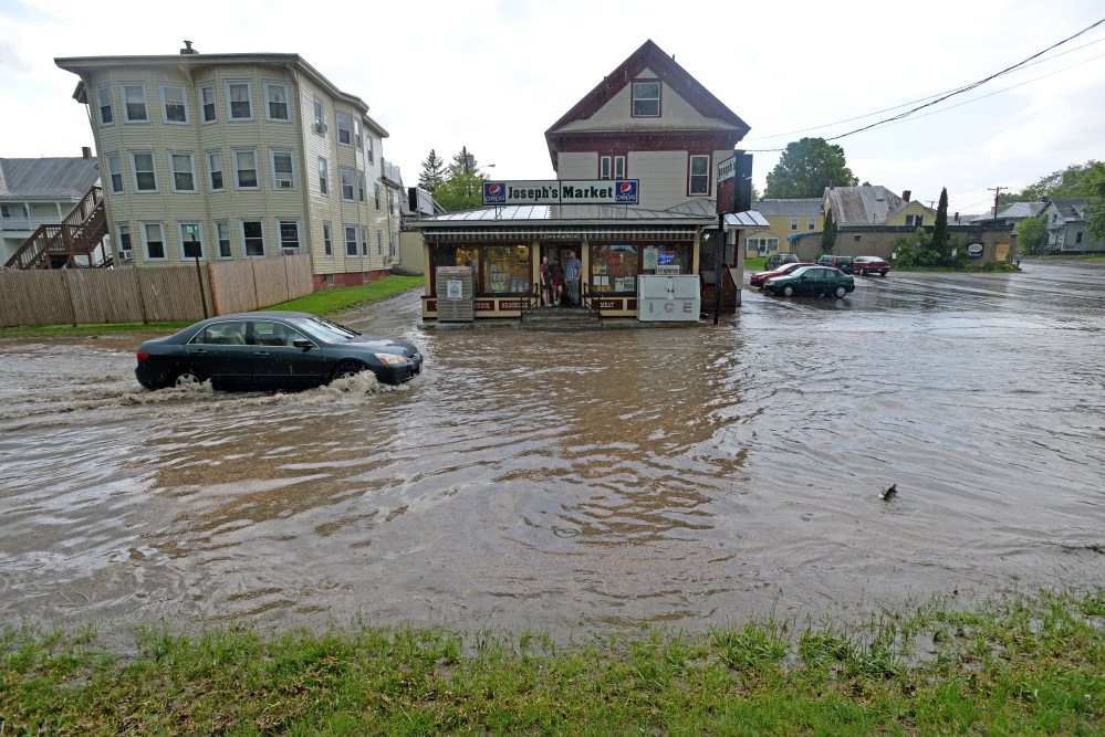 A car drives on flooded Front Street May 28 as heavy rain moved through Waterville. Two downtown businesses are still repairing damage from flooding in their building from the storm.