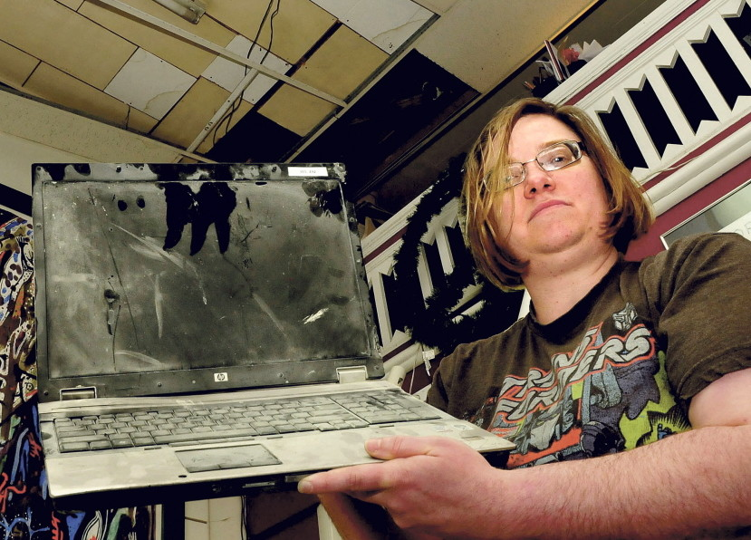 Amy Cyrway, co-owner of the Framemakers in Waterville, Monday holds a laptop computer that shorted out and caught fire after rain water flooded the store on May 28. There was substantial damage from the fire, and ceiling tiles, above, also collapsed. Employees covered the artwork inside.