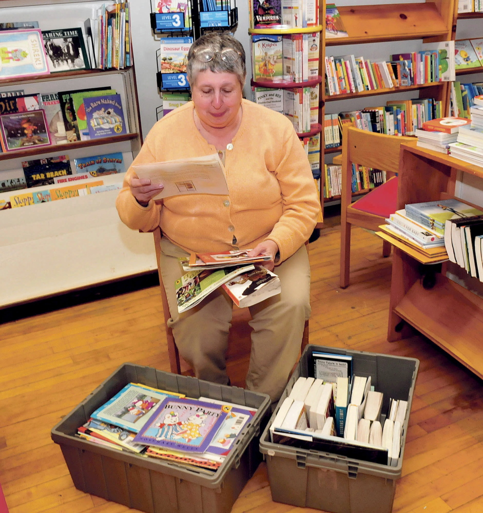 Ellen Richmond, owner of the Children's Book Cellar in Waterville, holds some of the books damaged when rain from a May 28 storm flooded the store. Richmond said the storm caused $1,000 of damage.