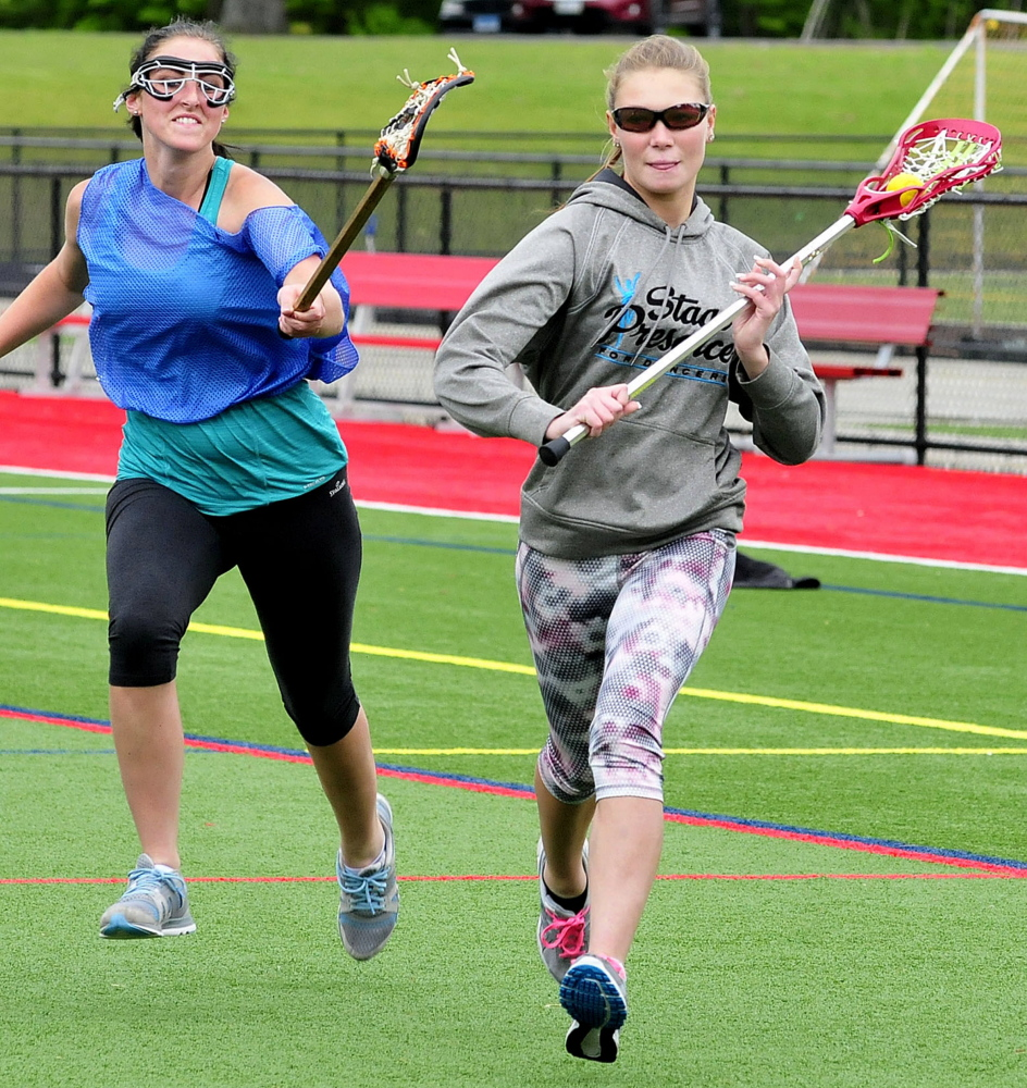 Winslow High School lacrosse players Victoria Lee-Bonsant, left, and Kameron Michaud run drills at practice Monday at Thomas College in Waterville.