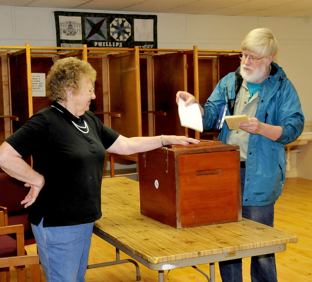 Phillips ballot clerk Lorraine Berry opens the ballot box for resident Alan Morse during SAD 58 budget voting on Tuesday. Residents of Phillips, Strong, Avon and Kingfield voted on the SAD 58 budget, which had been reduced from $9.4 million to about $260,000.