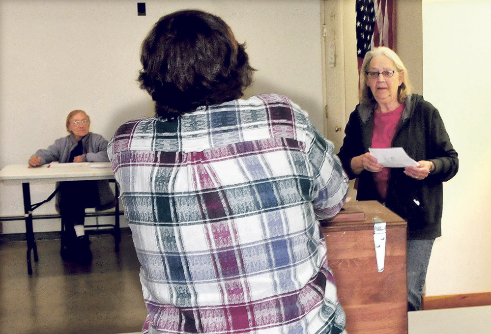 Resident Janne Haines, right, casts her SAD 58 ballot as clerk Marie Pillsbury opens ballot box in Avon on Tuesday. Clerk Josephine Gilcrest is in background. Haines was the eighth voter by 2 p.m. on a slow election day. Residents of Phillips, Strong, Avon and Kingfield voted on the SAD 58 budget, which had been reduced from $9.4 million to about $260,000.