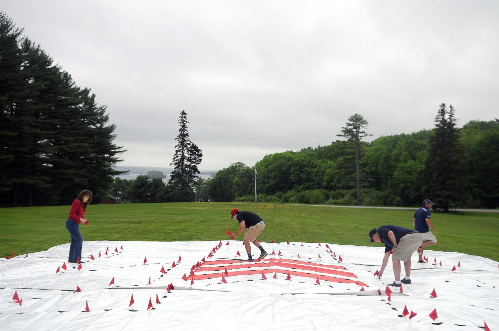 Members of the Boston Red Sox grounds crew stake out the lawn Tuesday at the Travis Mills Foundation National Family Retreat Center in Rome. The Fenway Park crew created a stencil to kick off the renovation and restoration of the retreat for combat-wounded and disabled veterans and their families.