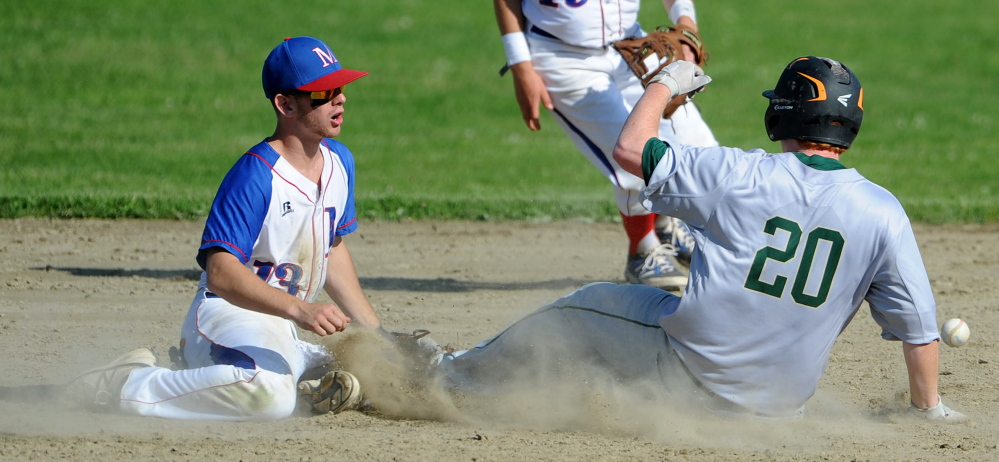 Staff photo by Michael G. Seamans   Oxford Hills' Emery Chickering (20) slides safely into second base as Messalonskee's Ben Frazee tries to dig the ball out of the dirt during an Eastern A quarterfinal game Thursday in Oakland.