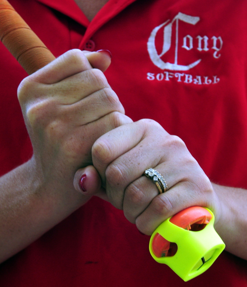 The Zepp sensor is seen on the end of bat held by Cony softball assistant coach Siobhan Murtiff on Thursday at Cony Family Field in Augusta.