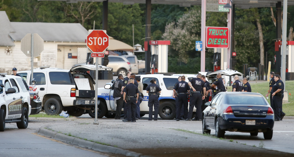 Police block the intersection of Dowdy Ferry Rd and Interstate 45 during a standoff with a gunman barricaded inside a van on Saturday in Hutchins, Texas. The gunman allegedly attacked Dallas Police headquarters.