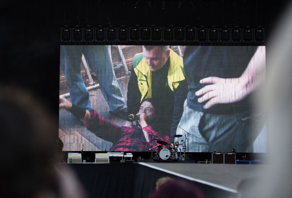 Foo Fighters' Dave Grohl is pictured on a big screen talking in a microphone after falling from the stage, during the band's concert at Nya Ullevi in Gothenburg, Sweden, on Friday. Grohl broke his leg in the fall.
