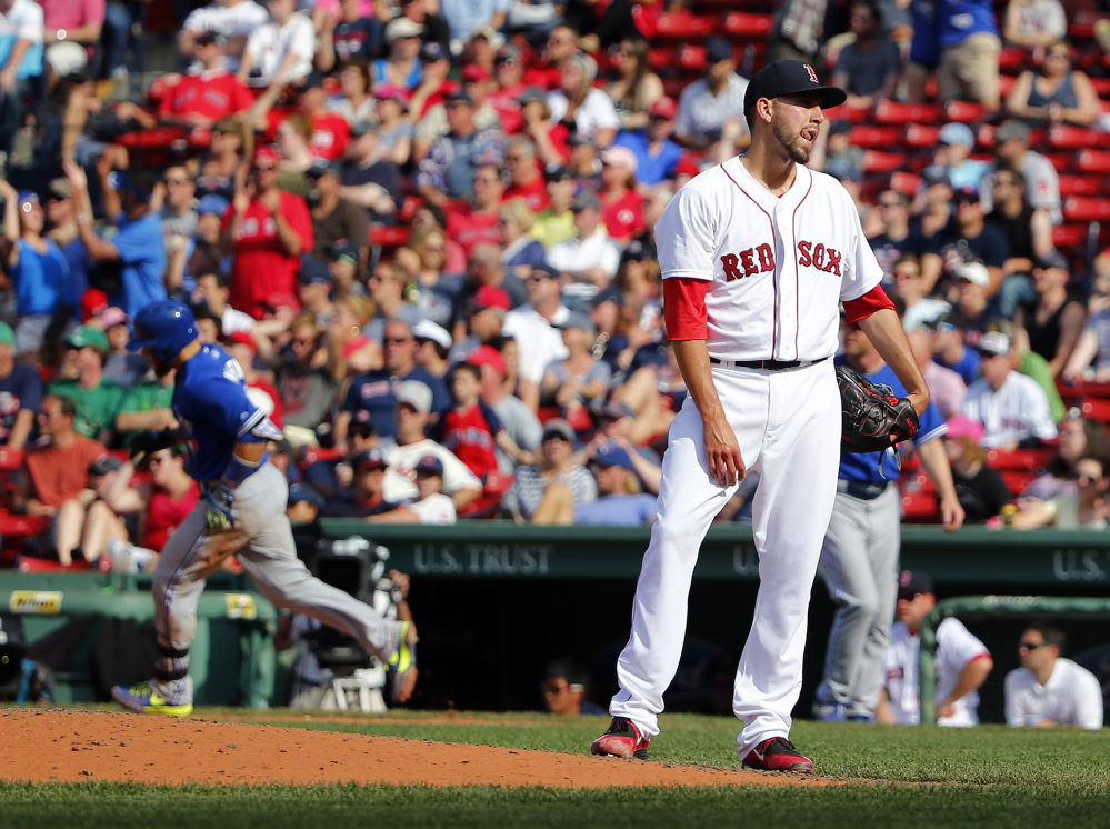 Boston Red Sox relief pitcher Matt Barnes stands on the mound after giving up the winning home run to Toronto Blue Jays' Russell Martin, left, during the 11th inning of Toronto's 5-4 win in a baseball game at Fenway Park in Boston Saturday.
