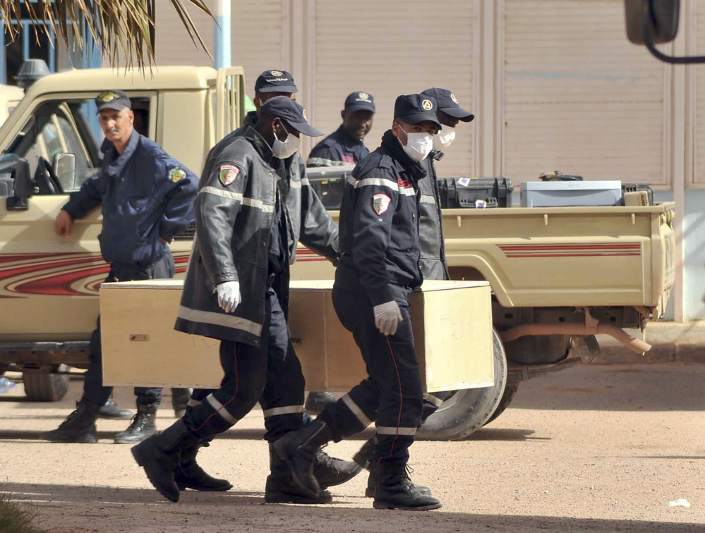In this Jan. 21, 2013 file photo, Algerian firemen carry a coffin containing the body of a person killed during the gas facility hostage situation at the morgue in Ain Amenas, Algeria.