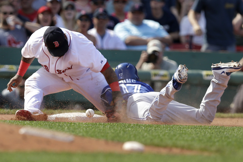 Boston's Pablo Sandoval, left, is unable to tag Toronto's Ryan Goins, right, as Goins advances to third base on an error in the seventh inning Sunday at Fenway Park in Boston.