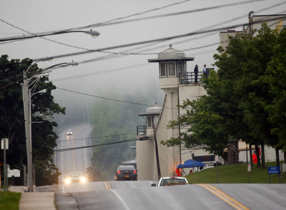 Vehicles drive past Clinton Correctional Facility on Monday, in Dannemora, N.Y.