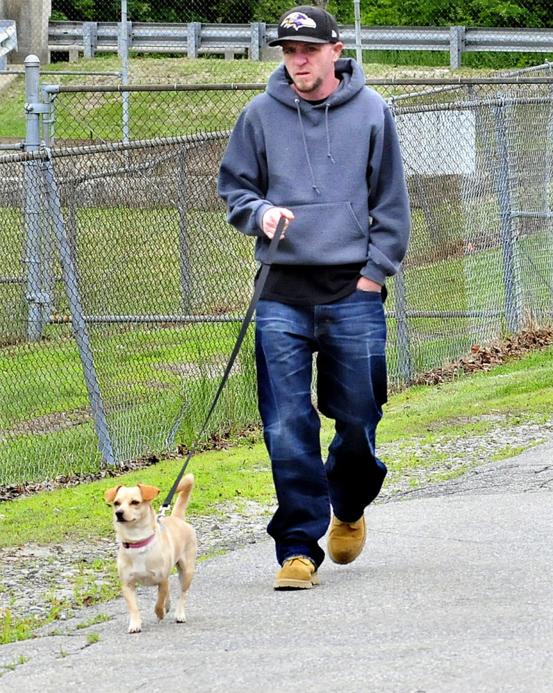 A man takes his dog for a walk past the Oakland Town Office on Cascade Mill Road Monday. The council passed an amendment to the town's animal control ordinance requiring dog owners to clean up after their pets.