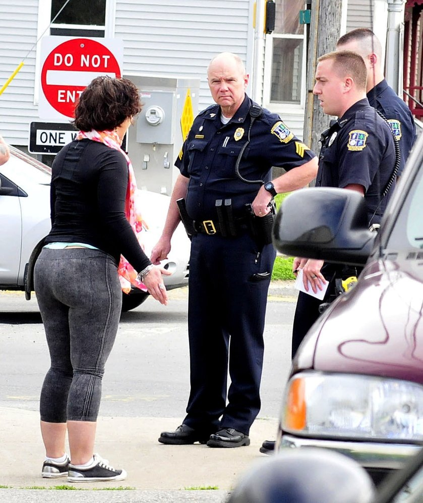 Waterville police talk to Codi Parker, who was later arrested and charged with domestic assault after a confrontation with a former boyfriend on Spring and Elm streets in Waterville on Monday. Parker screamed rape allegations to a growing crowd and allegedly hit the man before police calmed her down.