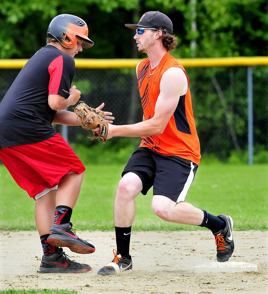 Winslow High School shortstop Alex Berard, right, tags a baserunner out during practice Monday.