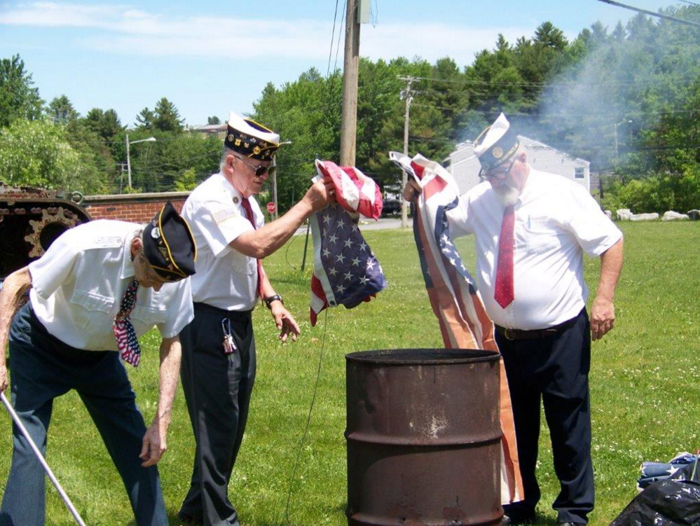 Fitzgerald Cummings American Legion Post 2 held a flag retirement ceremony Sunday at its Post home in Augusta. From left are Legionnaires John Smith, Commander Pat Eisenhart and James Palmer as they burn worn and torn American flags.