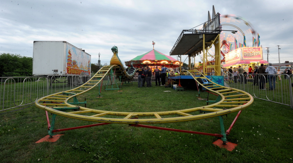 Inspectors from the Office of the State Fire Marshal investigate a ride malfunction at the Smokey's Greater Show carnival at Head of Falls in Waterville on Friday.