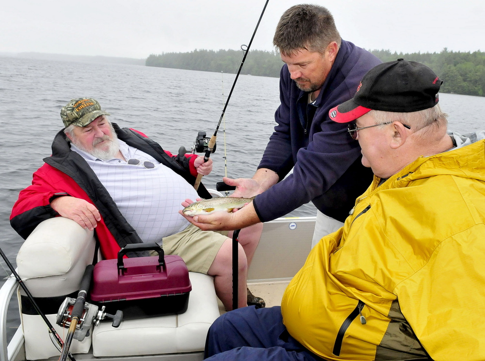 Volunteer boat captain Paul Stevens, of Belgrade, center, shows the brook trout that veteran Linwood Brayall, right, of West Gardiner, caught Tuesday on Great Pond in Belgrade. At left is veteran Carl Pettengill, of Farmingdale. The men took part in the Fishing Extravaganza, which provides an opportunity to relax and socialize with other veterans.